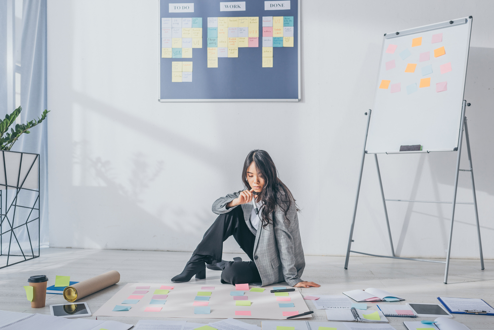 Asian scrum master sitting on floor near gadgets and sticky notes
